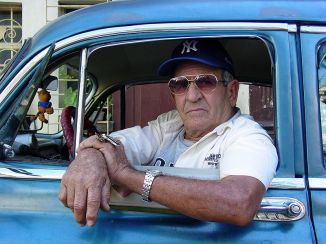 800px-Taxi_Driver_in_Classic_Car_-_Habana_Vieja_-_Havana_-_Cuba